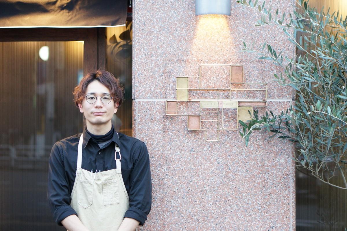オーナーシェフの石坂剛さん。右側の看板は銅板アーティストMABOさんの作品