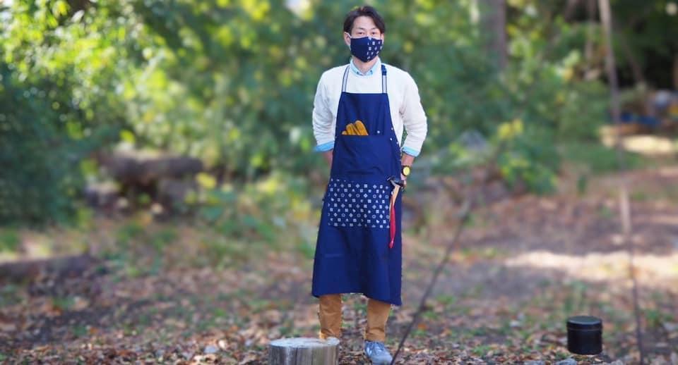アウトドアでも活躍するエプロンは、たたむとバッグになる。モデルは滝乃川学園の職員。