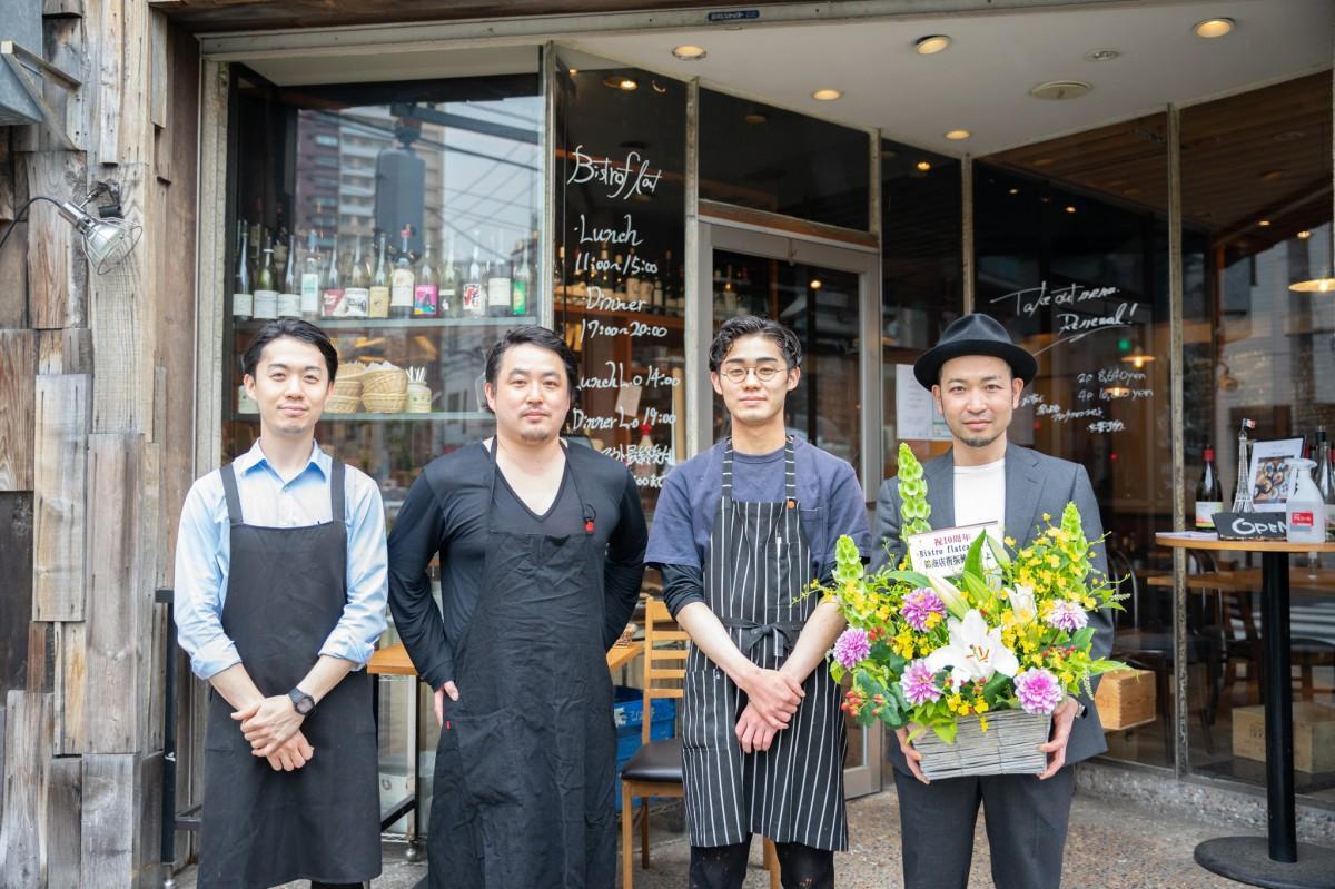 ビストロフラットのスタッフ。お祝いの花を持つ中沢さん。