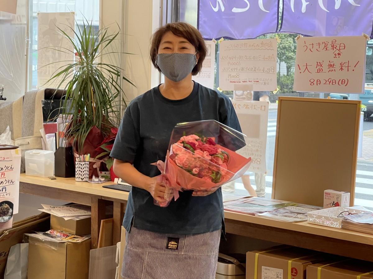 商店街メンバーから祝福を受ける店主の小川真智子さん