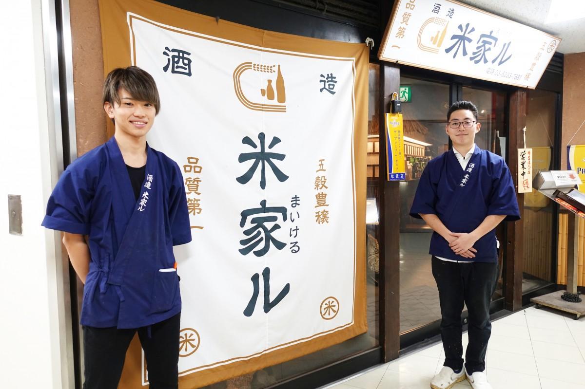 店の前に立つ「米と魚 酒造 米家ル 高田馬場店」の落合さんと井上さん(左から)