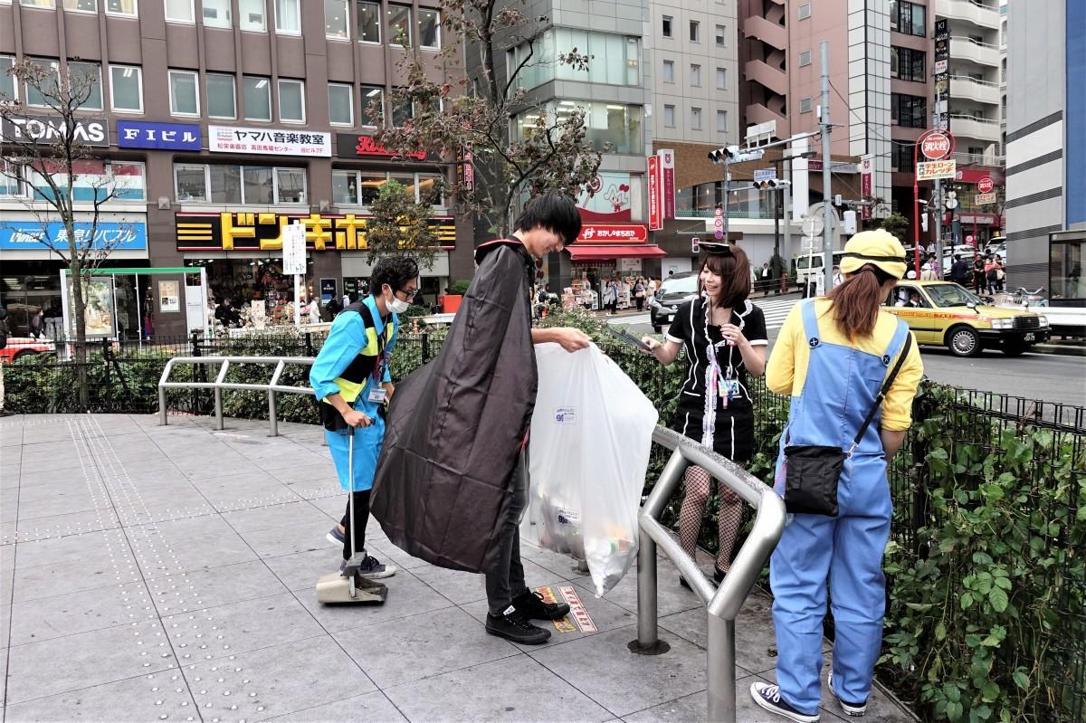 高田馬場駅前広場をハロウィーン仮装で清掃するスタッフ