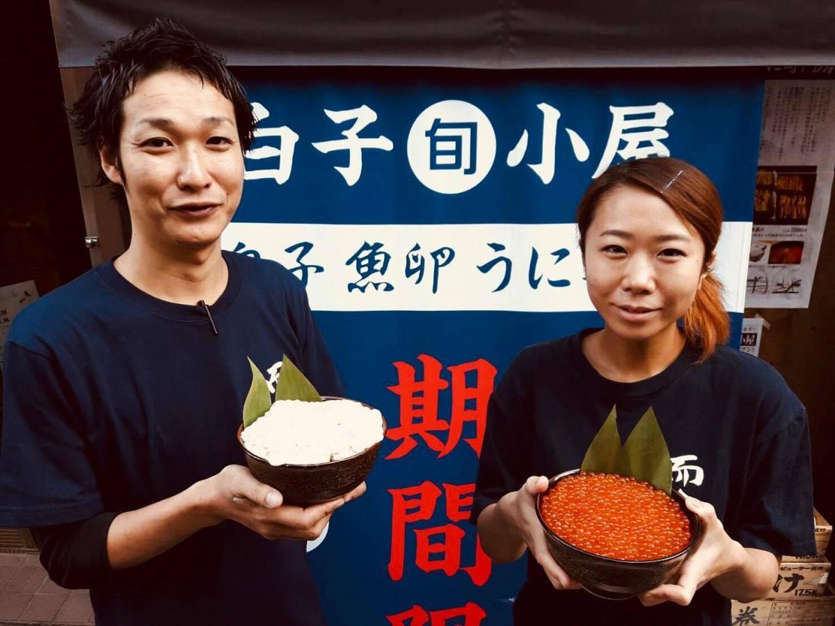 「白子『旬』小屋」の前で生白子、生イクラを持つ岡田幸之助さん、三浦摩耶さん(左から)
