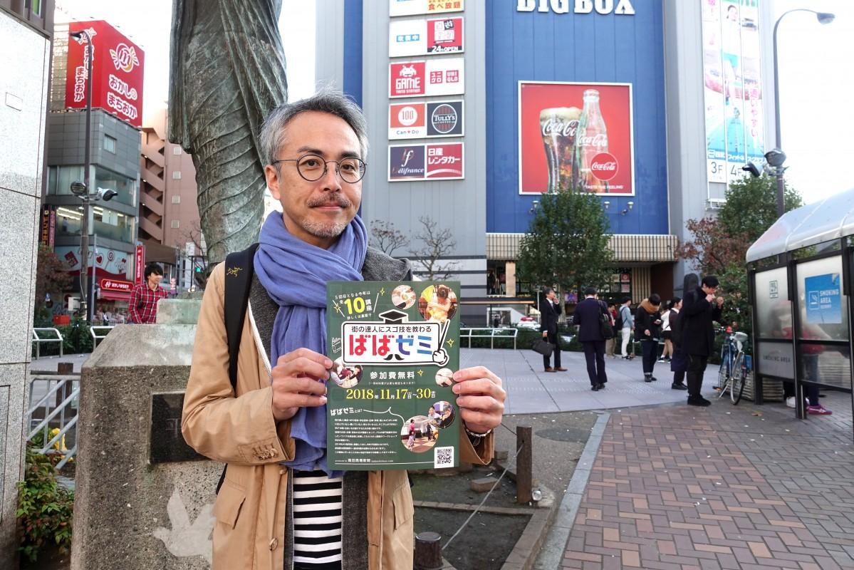 高田馬場駅前ロータリーで「ばばゼミ」のチラシを持つ高田馬場新聞の向井直也編集長