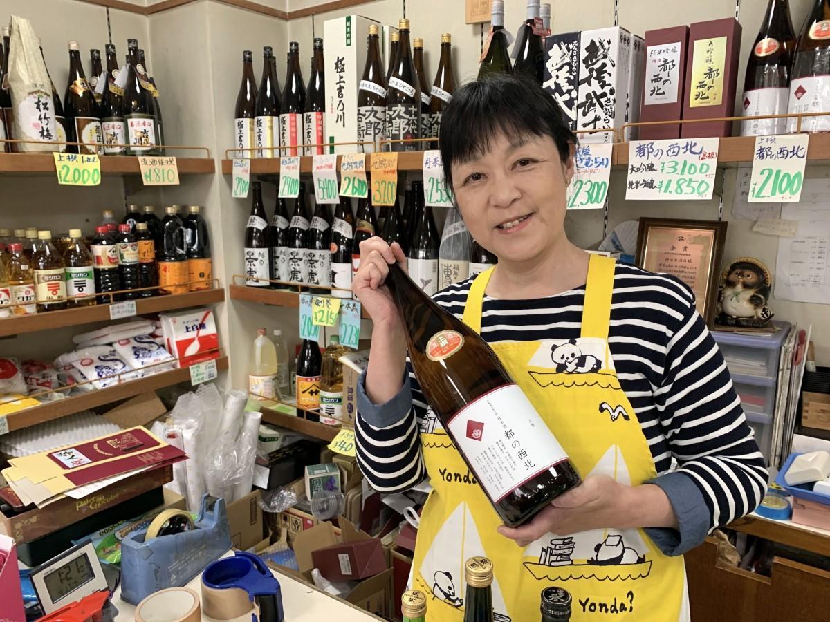 新しいラベルの「都の西北」を持つ野田屋酒店の古川智恵子さん