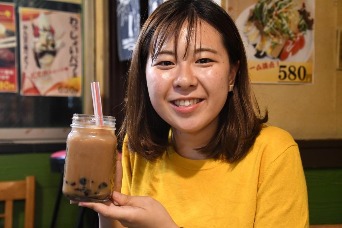 「わっしょい」でタピオカカルーアミルクティーを楽しむ早稲田大学創造理工学部の三村彩夏さん