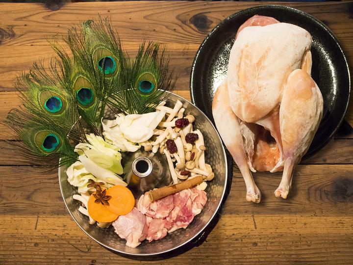 クジャクの羽も添えられた「火の鳥鍋」。提供時、肉はさばき、羽は装飾として添える。