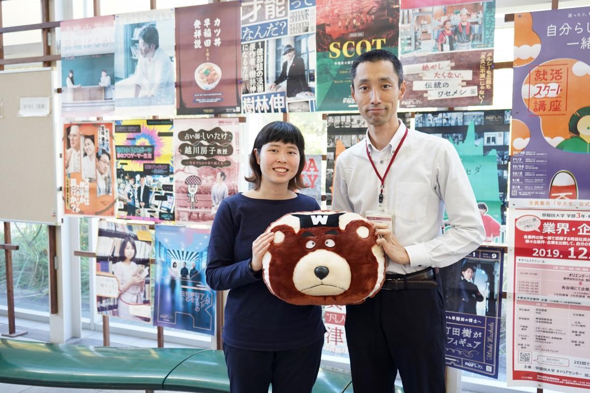プレゼントする「ワセダベアクッション」を手にする「早稲田ウィークリー」学生スタッフの文学部3年・我妻はなさんと学生生活課の布施直人さん(左から)