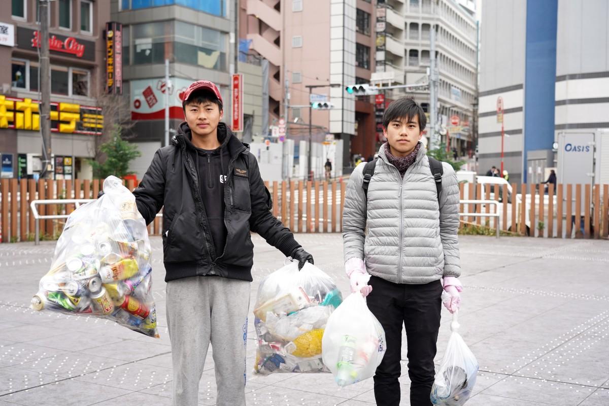 駅前ロータリーを清掃する早大サークル「ロータリーの会」の新井国憲さんと高橋永遠(とわ)さん(左から)