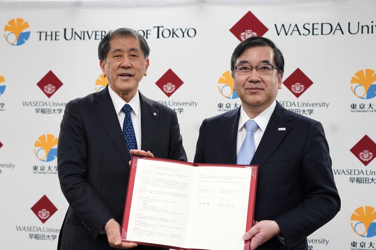 サインした協定書を持つ早稲田大学・田中愛治総長と東京大学・五神真総長(左から)