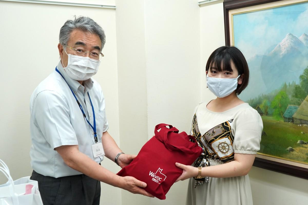 新宿社協の大野哲男次長にマスクを手渡すWAVOC学生リーダーの高山実女さん(左から)