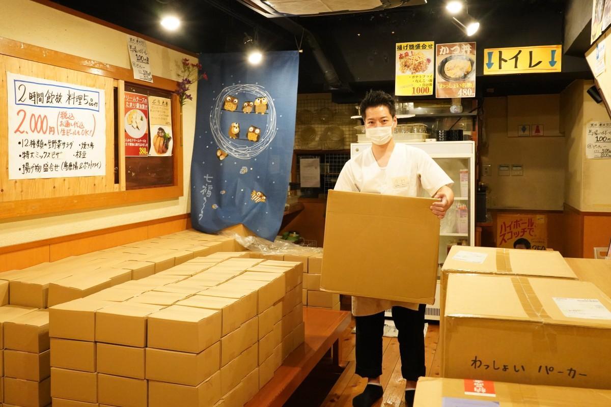 高田馬場の居酒屋「わっしょい」の1階店舗部分(通称:下わっしょい)でリターンの品物を持つ料理長の今村浩介さん