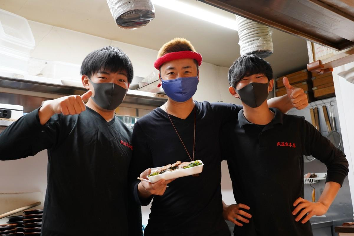 「武道家弁当」を持つ店主の滝坂滋晃さんと武道家のスタッフの皆さん