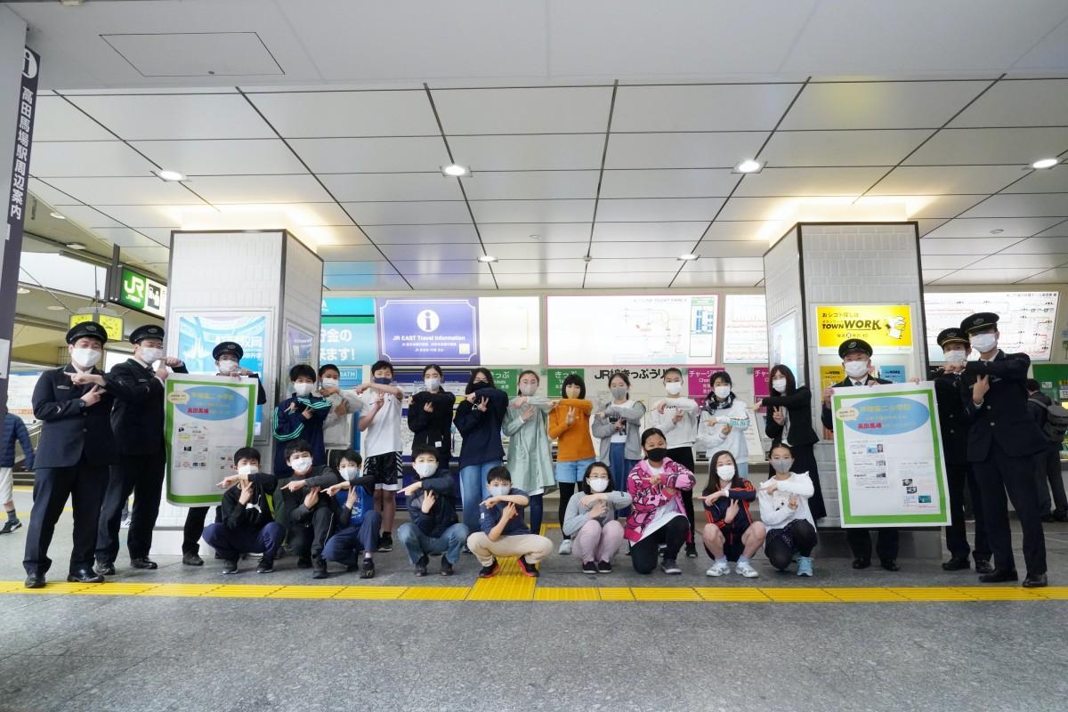 戸塚第二小学校6年2組の皆さんとJR高田馬場駅職員の皆さん(ポーズは戸塚第二小学校の「T」で、指の形は「二小」「2組」「21人」「テーマのNO.1」の意味を込めた)