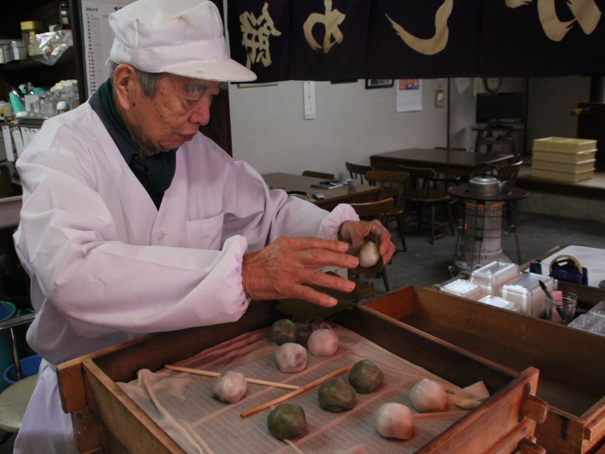 かしわ餅を包む山本さん