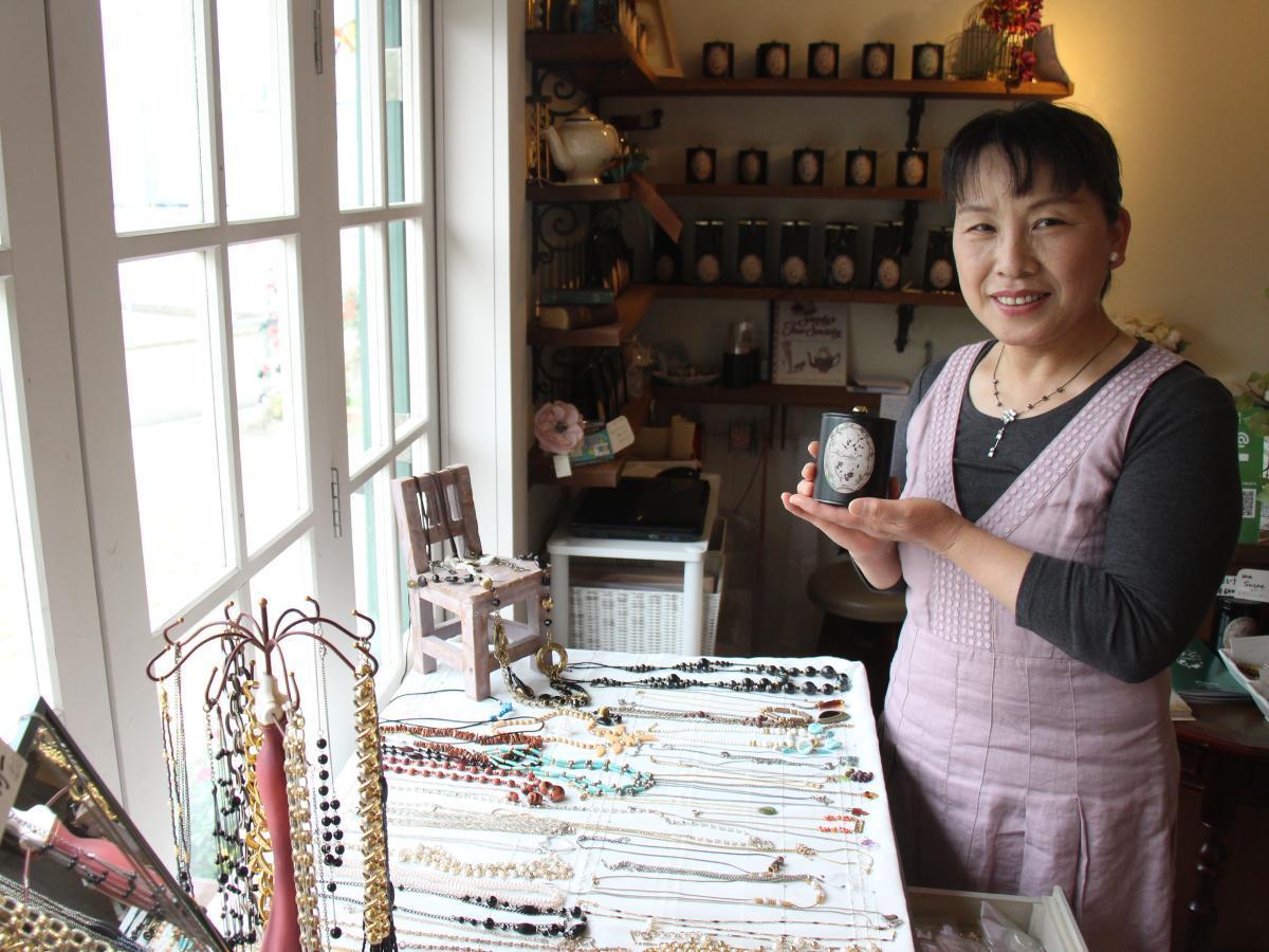 紅茶とアクセサリーを見せる店長の高橋美恵さん