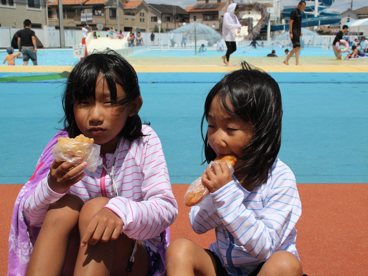 市民プールで揚げパンを頬張る子ども