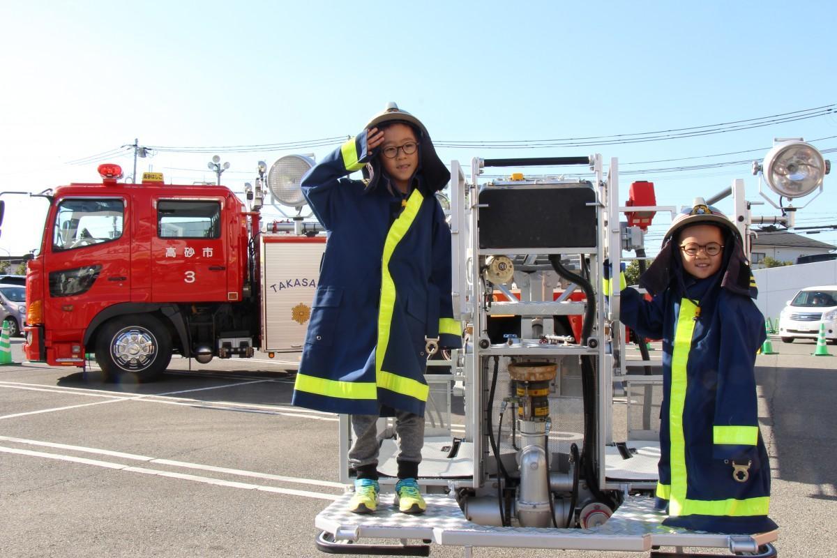 消防服を身にまとってはしご車の体験をする兄弟