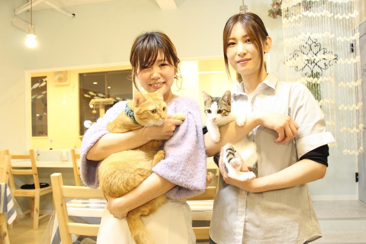 保護ネコを抱く村田サヤカさん(左)と山本歩実さん(右)