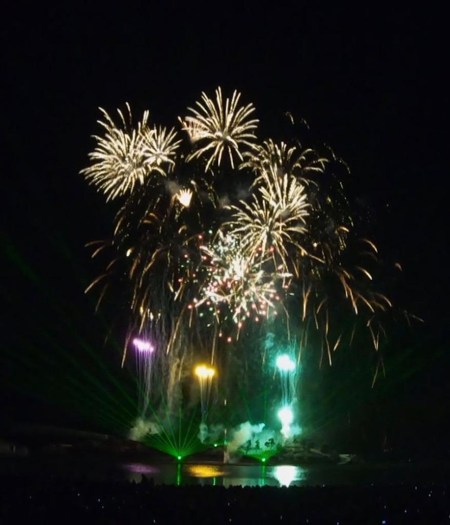 花火とレーザー光線が浜辺と夜空に浮かぶ