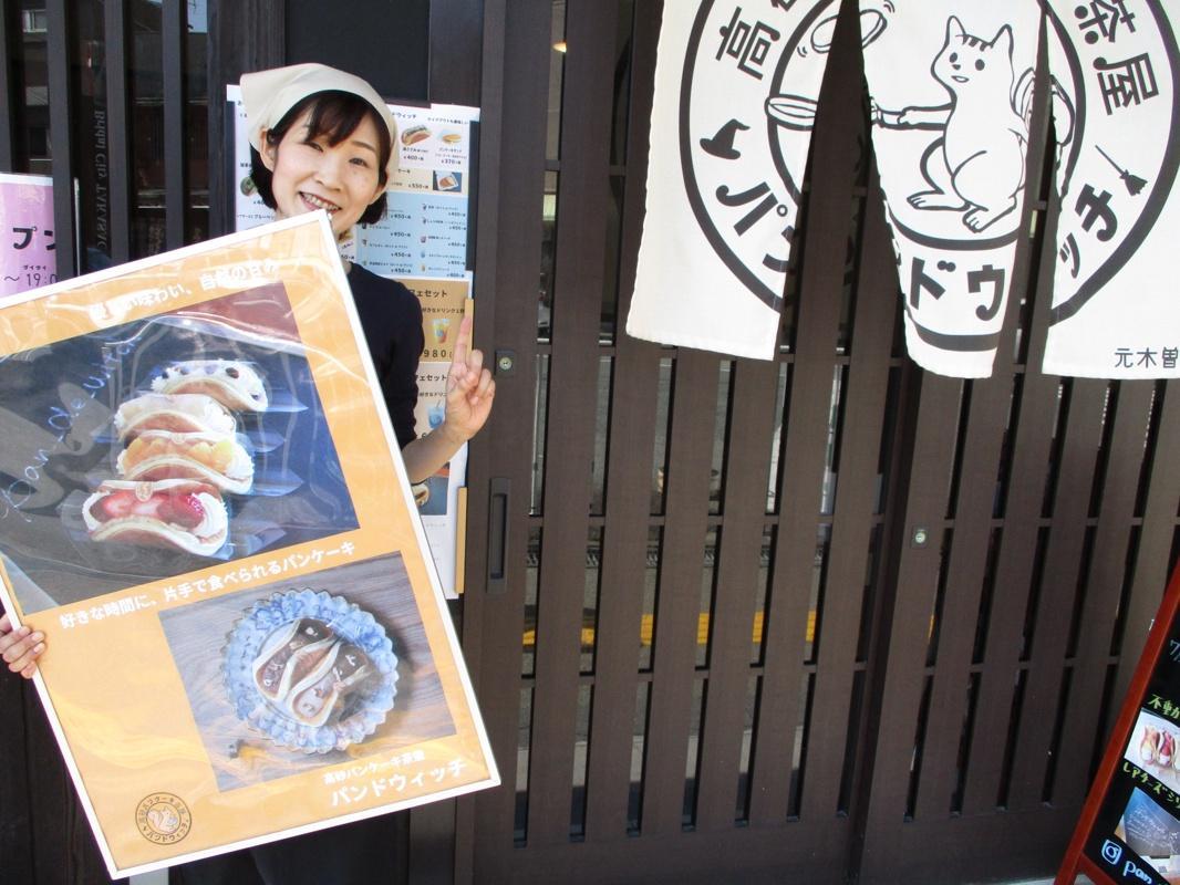 1周年のポーズをする笑顔の大江さん