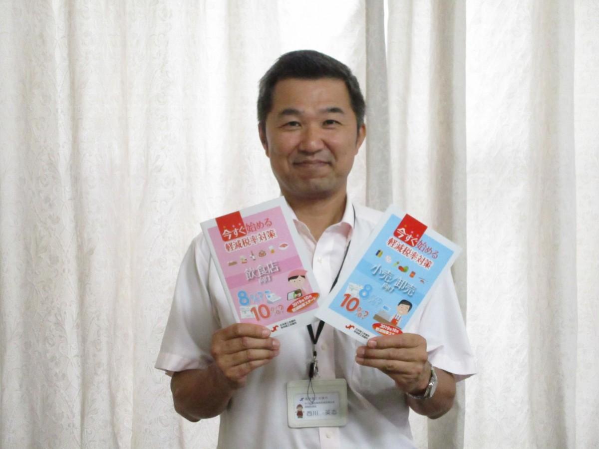 軽減税率対策の冊子を持ちPRする西川さん