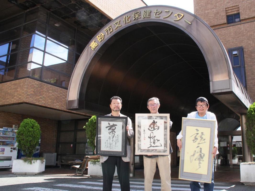 作品を手に来場を呼び掛ける小嶋さん(左)、田中さん(中)、大道さん(右)