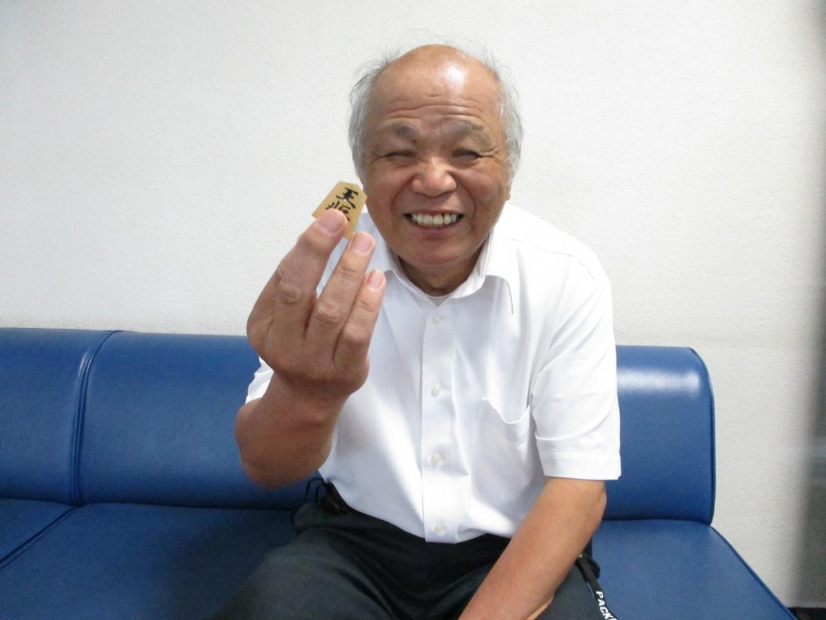 駒を手に笑顔の好田隆さん