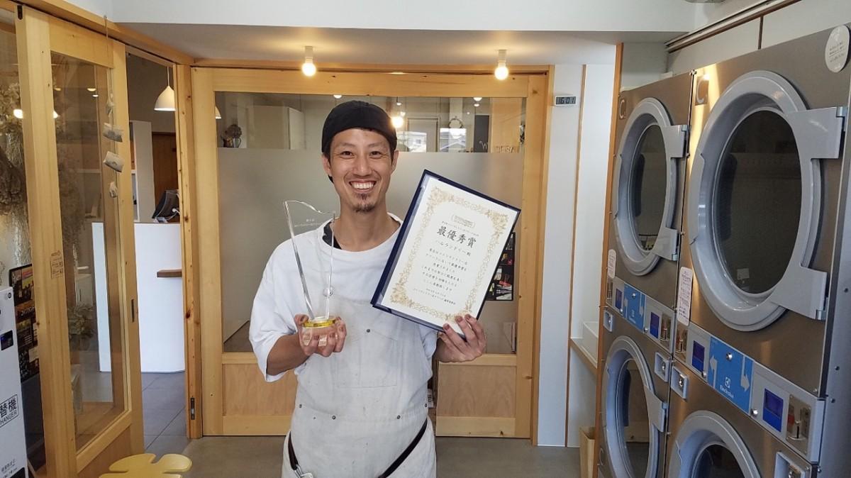 トロフィーと賞状を持つ店長の濱田さん