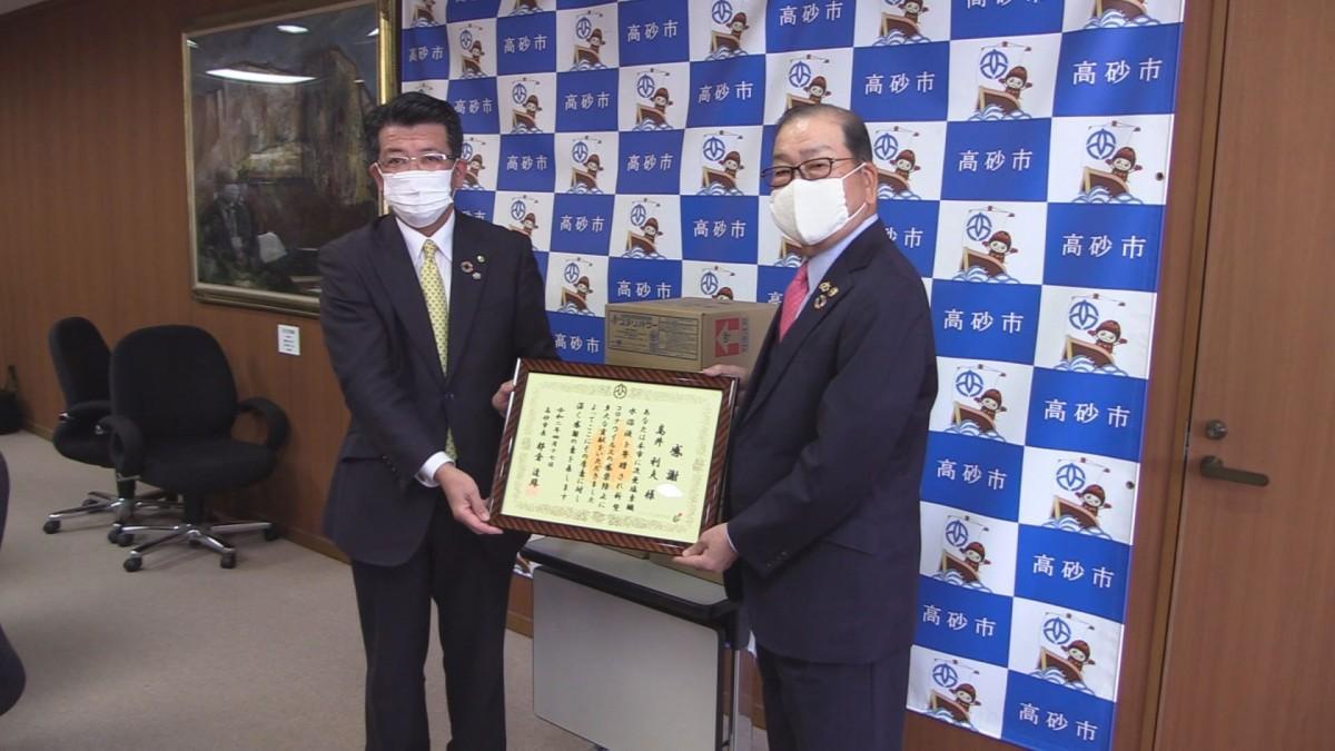 感謝状を受け取るケイ・ケイネットワークグループ会長の高井利夫さん(右)