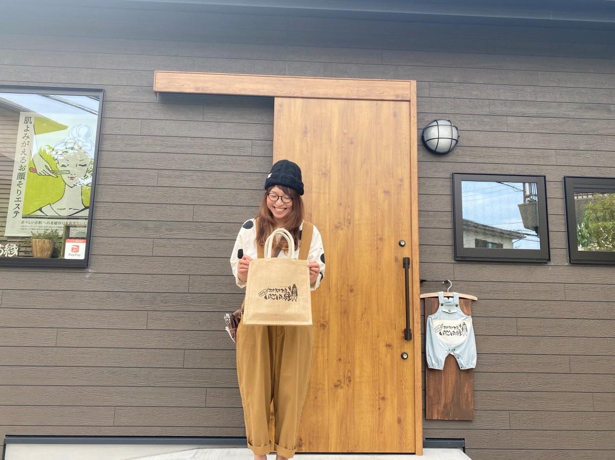 オリジナルジュートバッグを持ちアピールする春山さん
