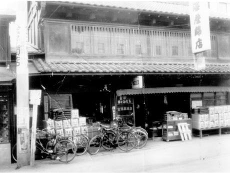 昭和30年頃の同店、店頭に積まれているのは綿の包み。昭和28年まで前の通りには路面電車が走っていた