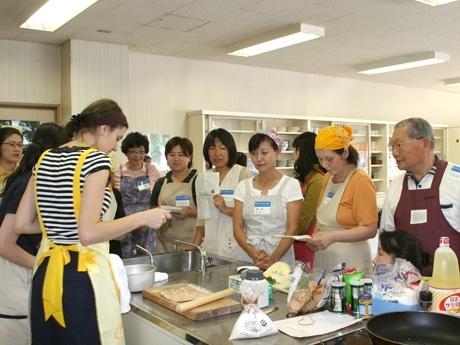 アリスさん(左手前)からルーマニア料理の手ほどきを受ける参加者たち。アリスさんは料理だけでなく日本語も上手