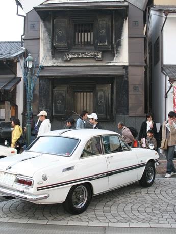 南銀座通りは蔵を改装した店舗や和風のしつらえの店舗が並ぶ雰囲気のある通り。クルマはマニアに「足回り」をのぞき込まれたISUZUベレット1600GTR(昭和45年製)