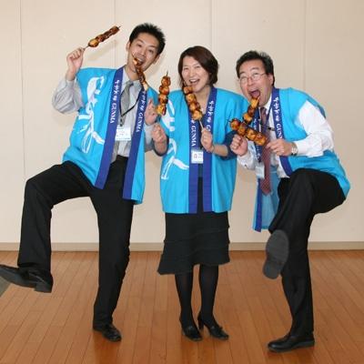 焼きまんじゅうの串を手に観光課のはっぴをまとい「焼きまんじゅうサミット」をアピールする、右から佐藤武夫さん、桑名かおりさん、佐藤学さん