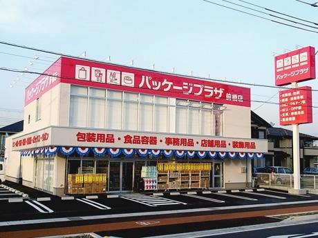 白い外壁に赤のオビと文字が目を引く「パッケージプラザ前橋店」