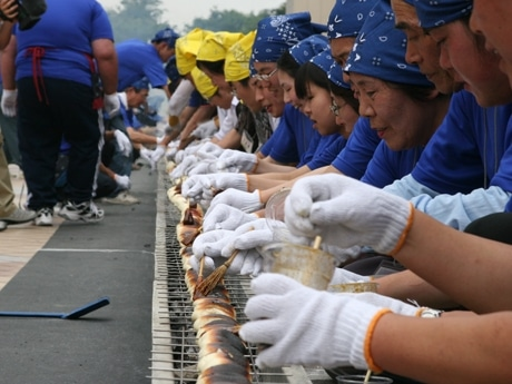 どんなに長くても伝統的な焼き方にこだわるのが、「いせさき焼きまんじゅう愛好会」のポリシー。この日も3度返す。ミニチュアの竹箒のようなはけで味噌を塗る