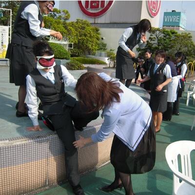 アイマスクを着用した従業員を障害者に見立て、安全に誘導する訓練を屋上で