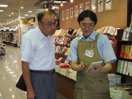 店頭で電子書籍専用端末「Lideo」を販売する煥乎堂。写真は「Lideo」の説明を聞く金井さん(前橋市粕川町)