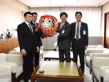 届けに来た警視庁捜査一課の二人(左)から「事件だるま」う受け取る山本龍前橋市長
