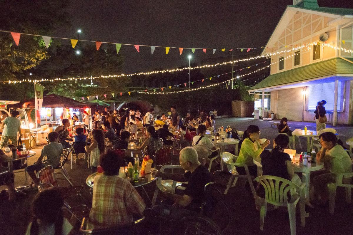 夜の遊園地でビールを楽しむ人たち