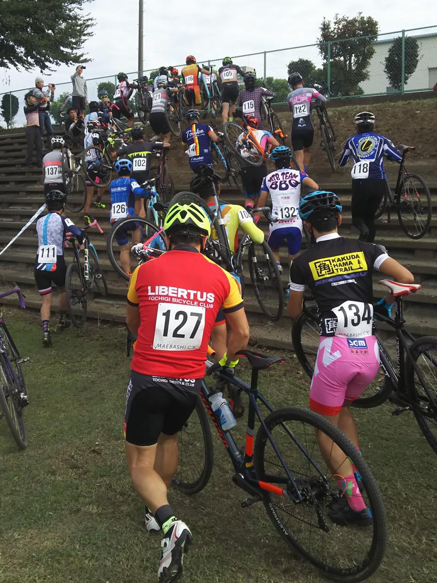 自転車を担ぎ、岩神緑地の石段を上る選手たち