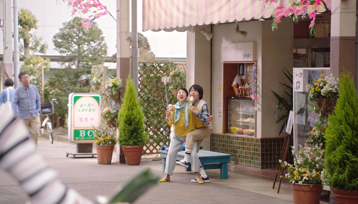 10年前の昔の写真と同じ構図の撮影するシーン。背景はポイントとなった「持ち帰り専用の販売口」