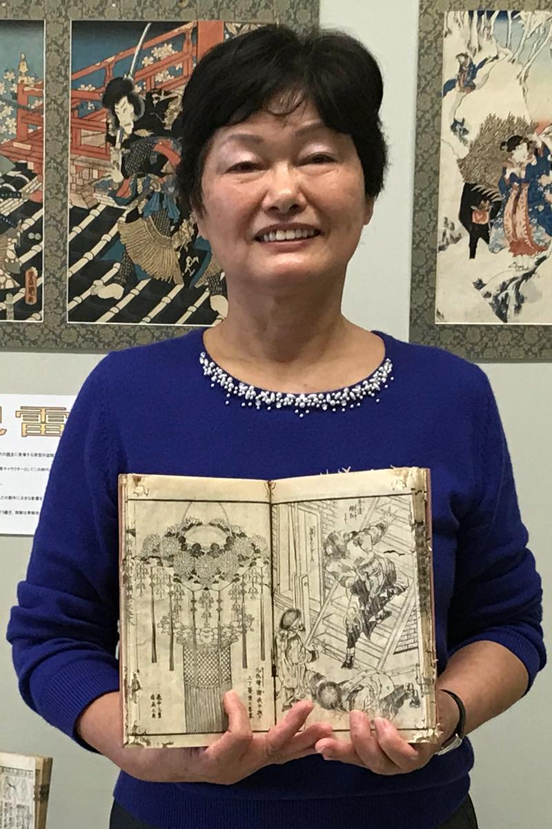 大学入試挑戦がコレクション展につながった林田知子さん。手にしているのは葛飾北斎が挿絵を描いた「水滸伝」