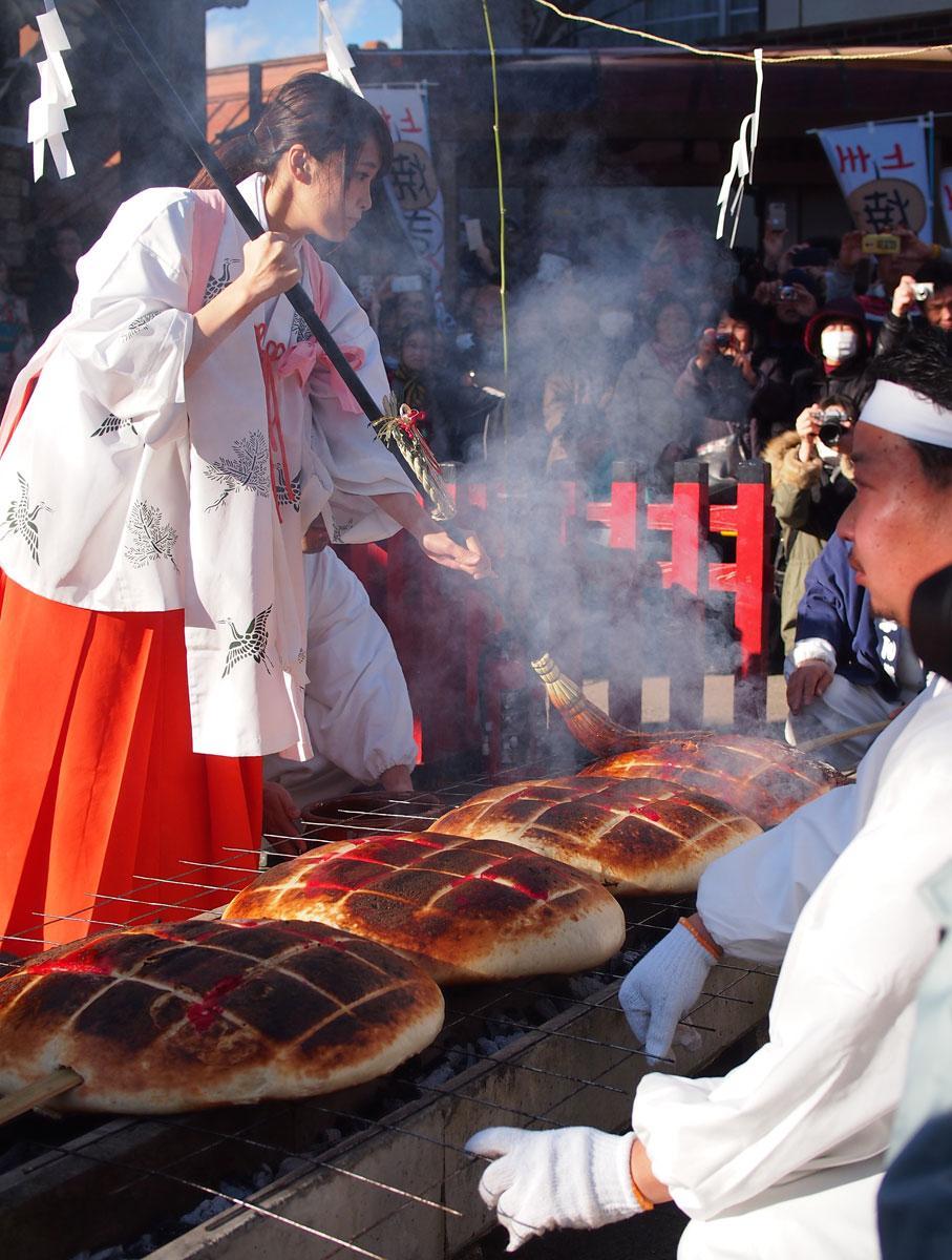 煙に巻かれても力強く巨大焼きまんじゅうを焼くのは巫女姿のミスひまわり