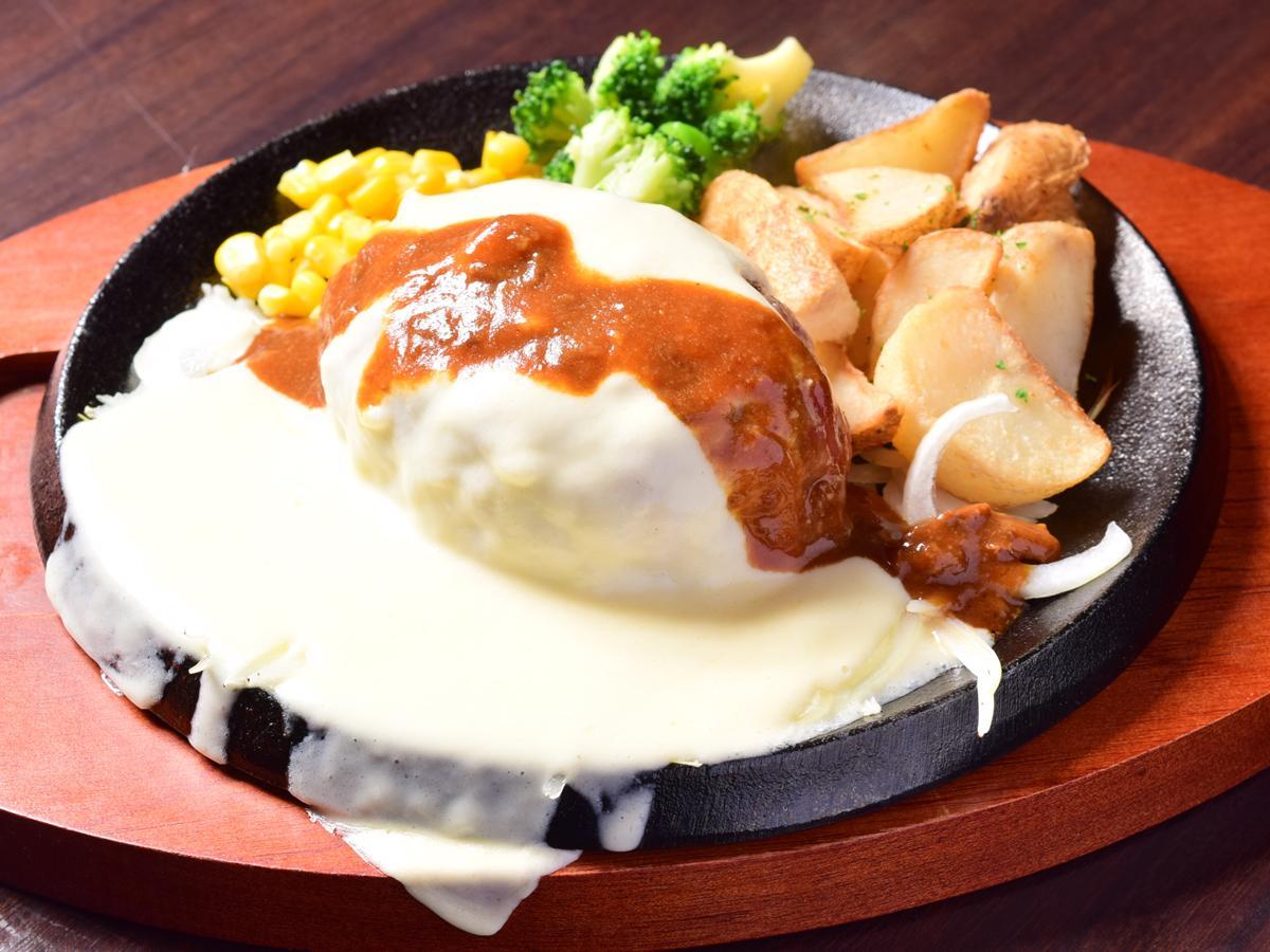 「超粗びき炭火熟成牛ハンバーグ とろとろチーズソース」(Mサイズ1,428円)、平日のランチタイムはライスまたはパン、スープが付く。ライスとスープはおかわり無料