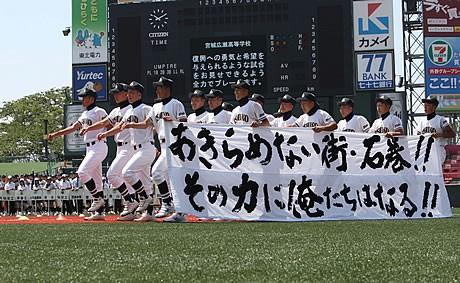 第93回全国高校野球選手権宮城大会開会式で、横断幕を持って入場行進する石巻工高の選手たち