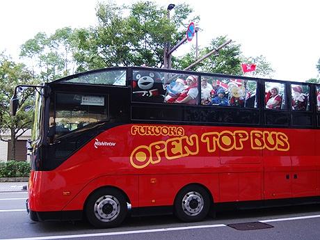 オープントップバスに乗るくまモンとサンタクロースら