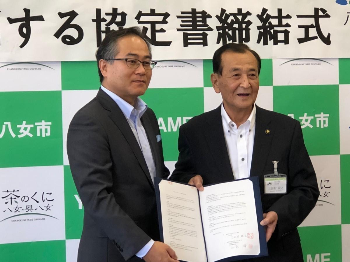 締結書を披露するKBCの和氣靖社長(左)と八女市の三田村統之市長