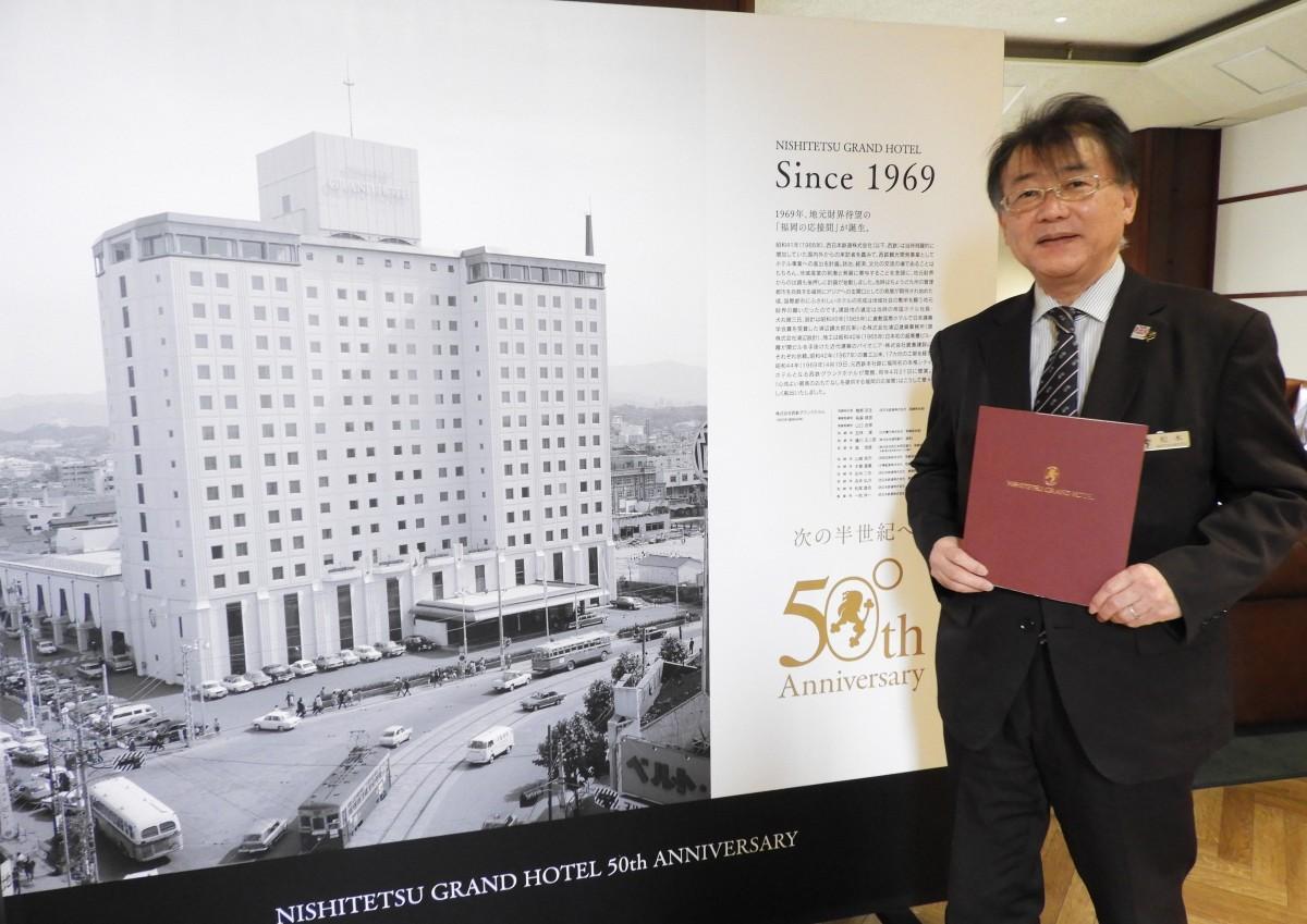 記念誌「Legacy」を紹介する西鉄ホテルズ営業戦略部の松本憲治さん